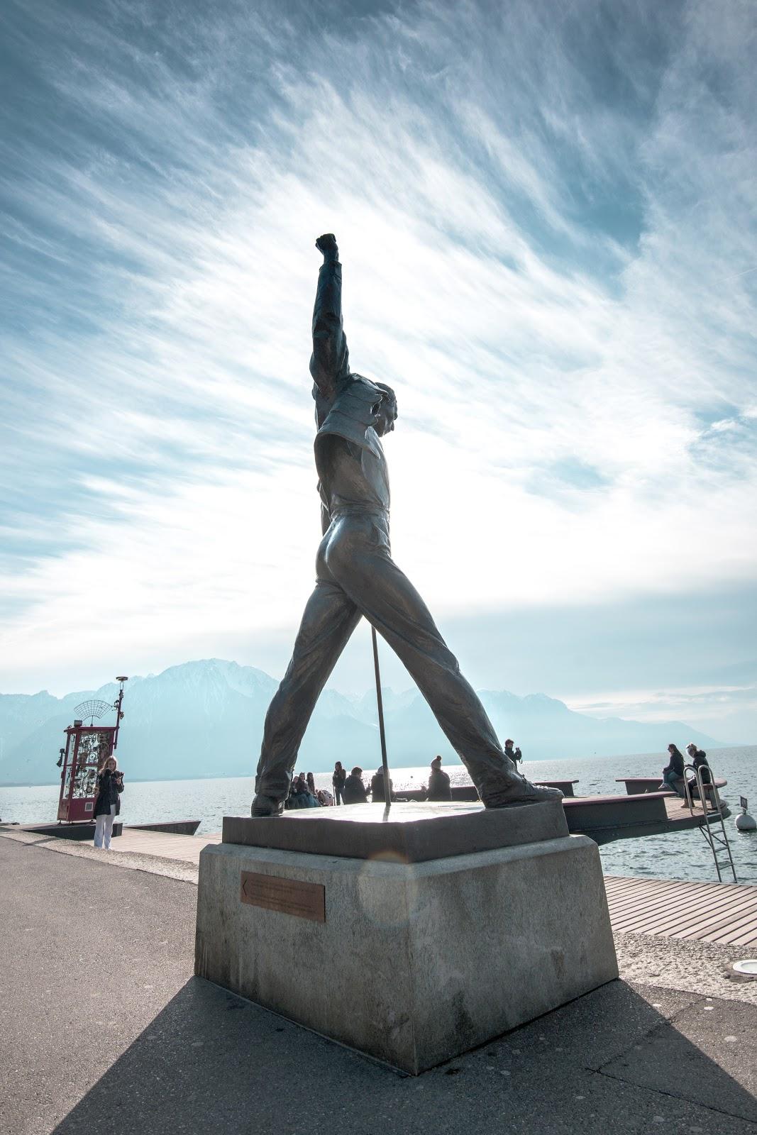 スイスのモントルーのレマン湖の畔の両足を開いて右手を上げたフレディ・マーキュリーの銅像