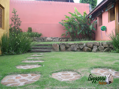 Muro de pedra com pedras rústicas com tipo de assentamento de pedra rústico com a escada de dormente, o caminho de pedra com pedra moledo e a execução do paisagismo em residência em Mairiporã-SP.