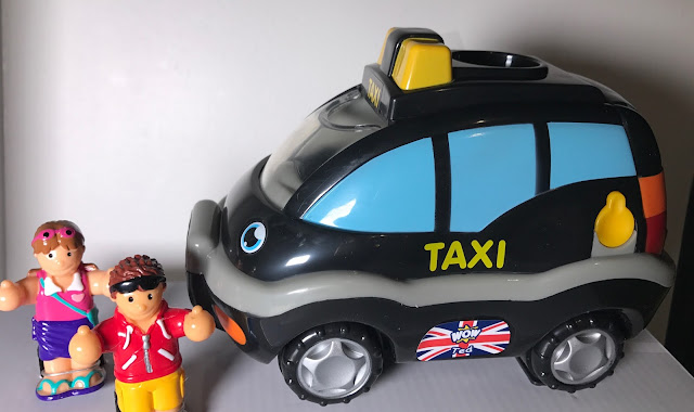 A toy black taxi and 2 tourist looking figures