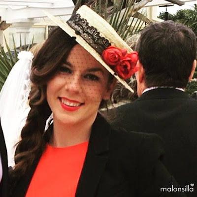 Invitada a boda de invierno con vestido rojo y americana negra. Peinado de trenza ladeada y sombrero de paja con encaje en negro y flores rojas.
