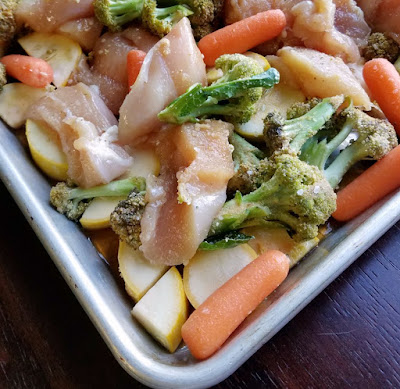 corner of sheet pan with raw chicken and veggies ready to cook