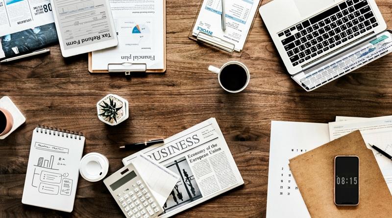Mesa de trabalho com blocos de anotações, planilhas e notebook