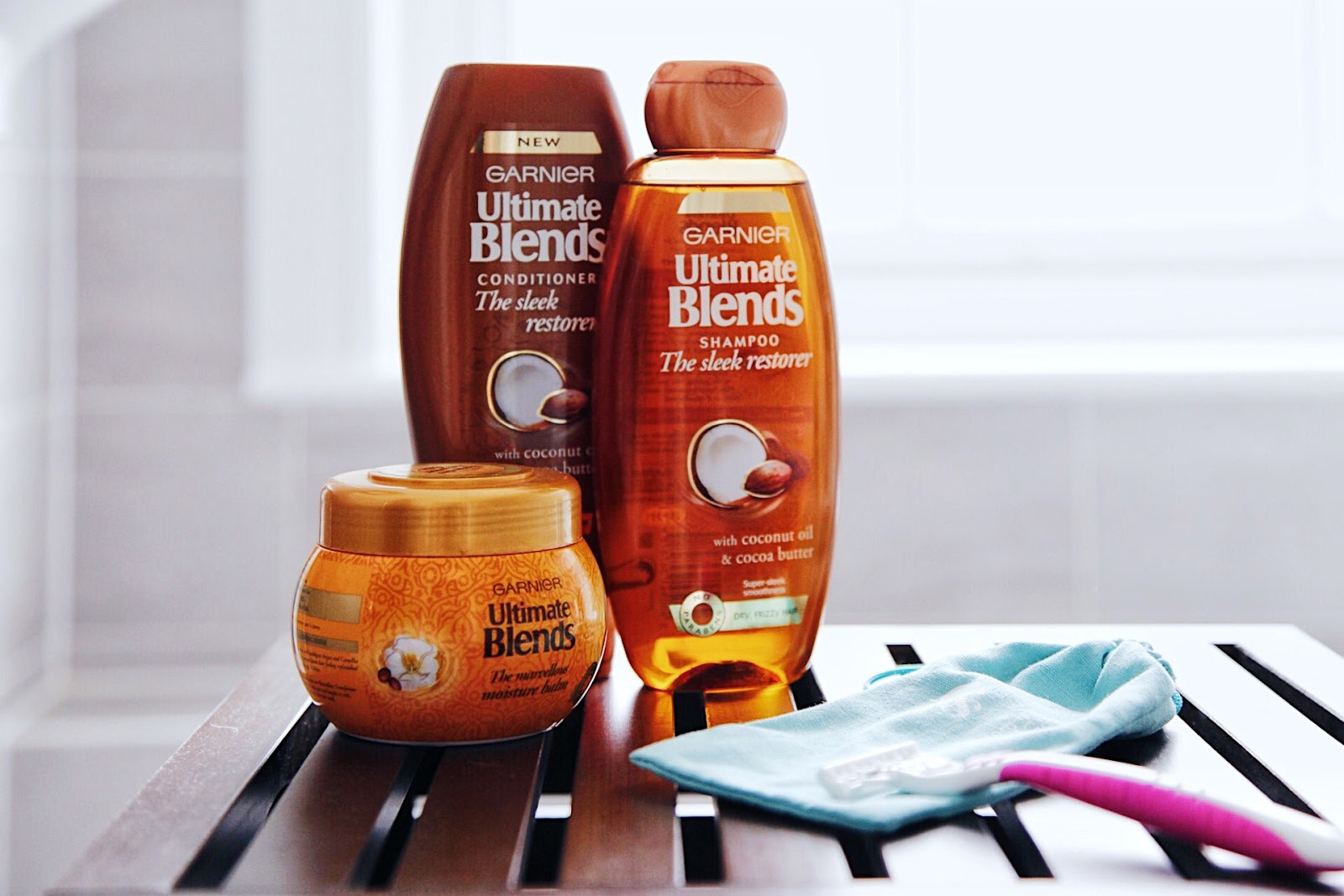 Garnier Sleek Restorer Shampoo and Conditioner on dark wooden box.