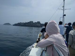 船の上から軍艦島を眺める私