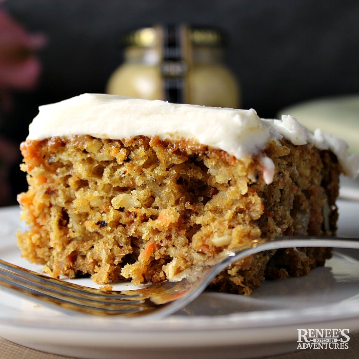 One slice of Dijon Carrot Cake sitting on a white plate with a fork. Dijon mustard jar in the background