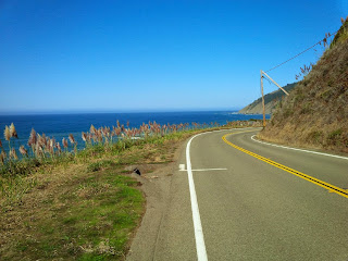 Empty coastal road in America against a clear, blue sky.