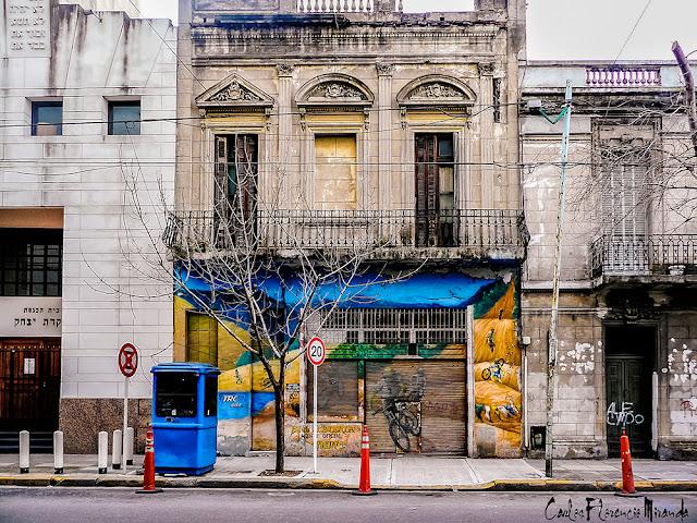 Edificio santiguo con pintura de un ciclista en el porton.l