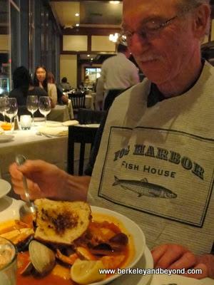 diner tucks into cioppino at Fog Harbor Fish House in San Francisco
