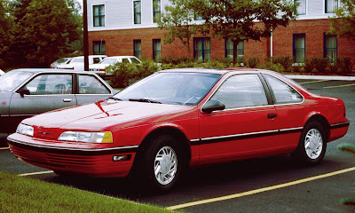 Red 1992 Ford Thunderbird parked in a crowded lot.