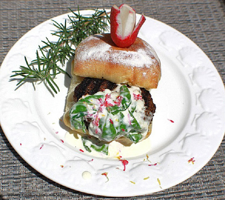 This is a hamburger on a white plate with spinach lemon cream sauce over the top with a sprig of rosemary on the plate on a ciabatta roll