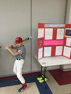Young boy dressed as a baseball player holding bat up in the air like going to bat