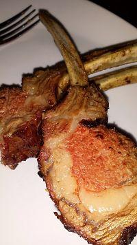 Chuletas de cordero sobre un plato. Encima del mismo se puede ver la punta de un tenedor