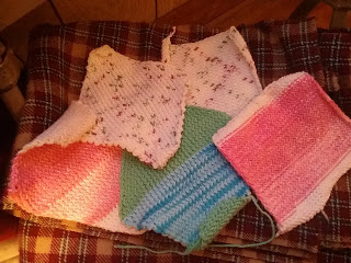 Five knit washcloths, square and diamond shapes- varigated pink-white and white-red-green colors.