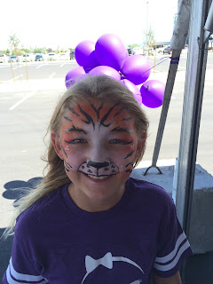 A young girl with her face painted like a Tiger