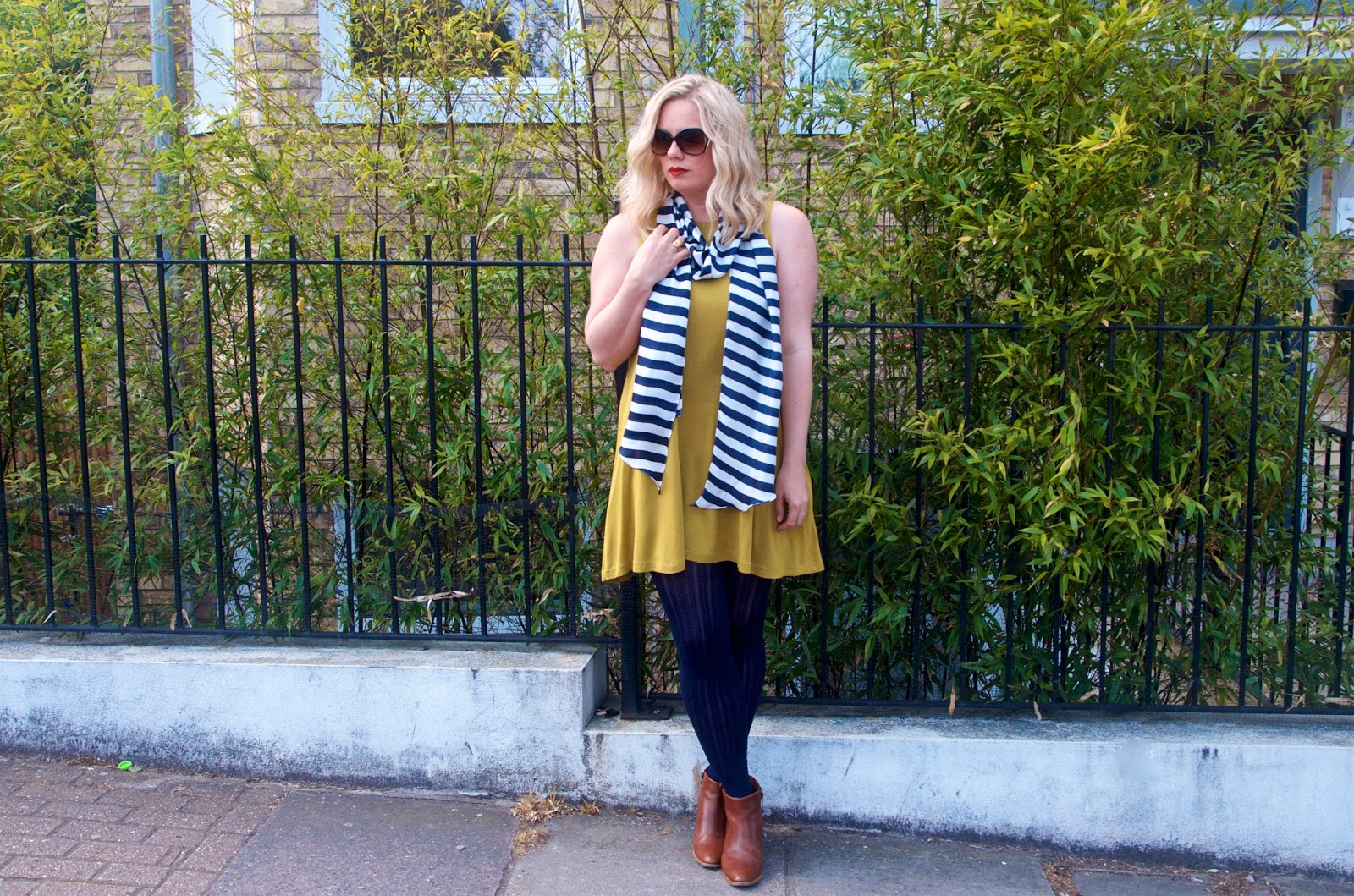 yellow dress, navy and white striped scarf, navy tights, brown boots and sunglasses