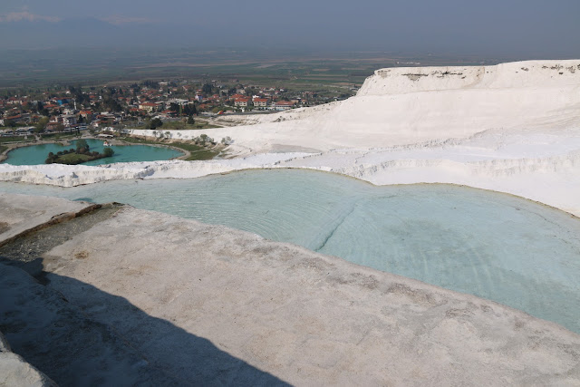Removing shoes before stepping into travertines terraces at Pamukkale Thermal Pools (Cleopatras) pools in Turkey