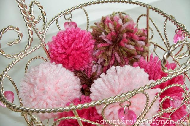 wire basket full of handmade pom poms
