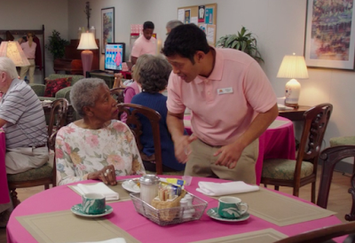Pillboi, wearing a pink polo shirt and khakis, is talking to an old black woman with short gray hair, sitting at a table with a pink tablecloth and various food-related objects, like salt and pepper shakers, on it. They're at an old folks home and there are multiple people in the background.