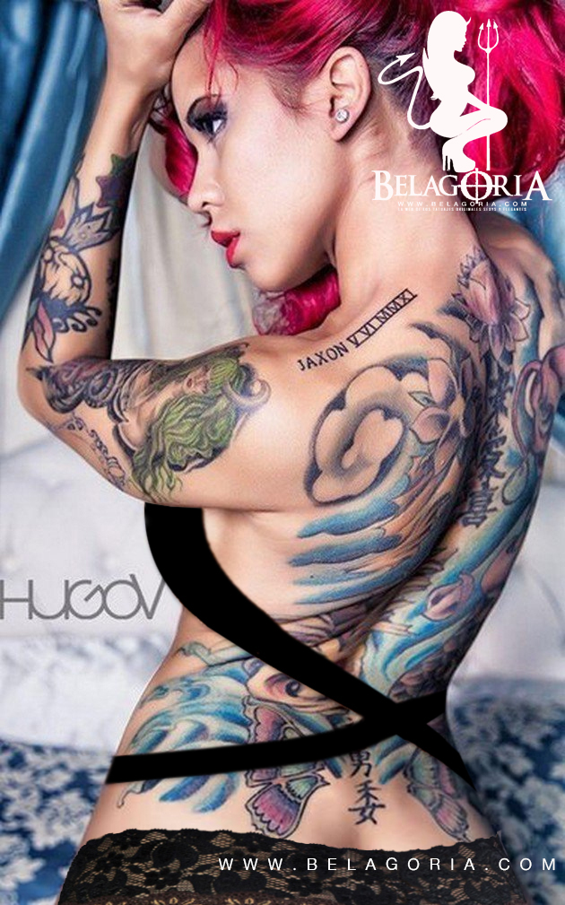 Foto de una modelo de pelo rosa esta posando , vemos su espalda con tatuajes