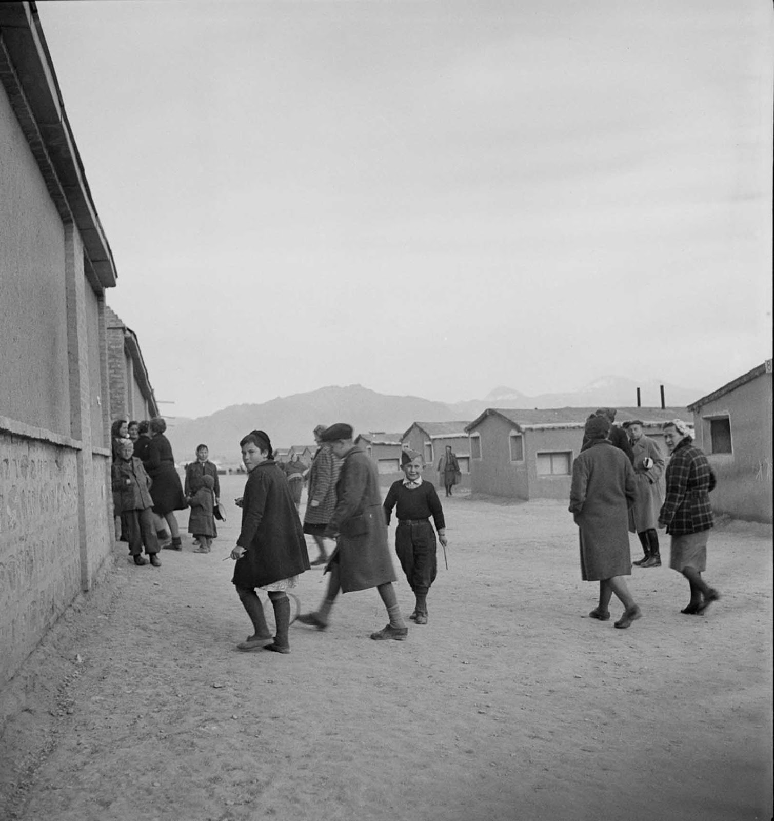Polish children play among the dormitories of a Red Cross camp.