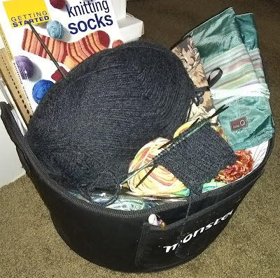 Black basket full of yarn and other knitting supplies, among them, a book, 'Getting Started Knitting Socks' by Ann Budd, a skein of charcoal-colored yarn and the beginnings of ribbed knitting, in charcoal, on green double-pointed needles