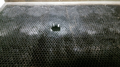 Hole burnt in the middle of a metal honeycomb grid
