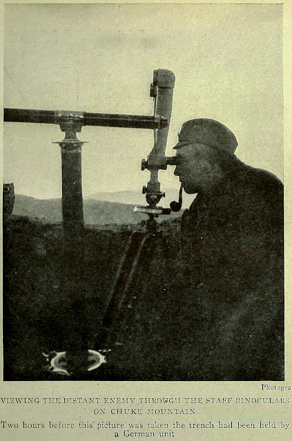 VIEWING THE DISTANT ENEMY THROUGH THE STAFF BINOCULARS ON CHUKE MOUNTAIN Two hours before this picture was taken the trench had been held by a German unit