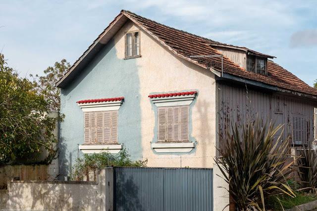 Casa de madeira com fachada em alvenaria e mansarda