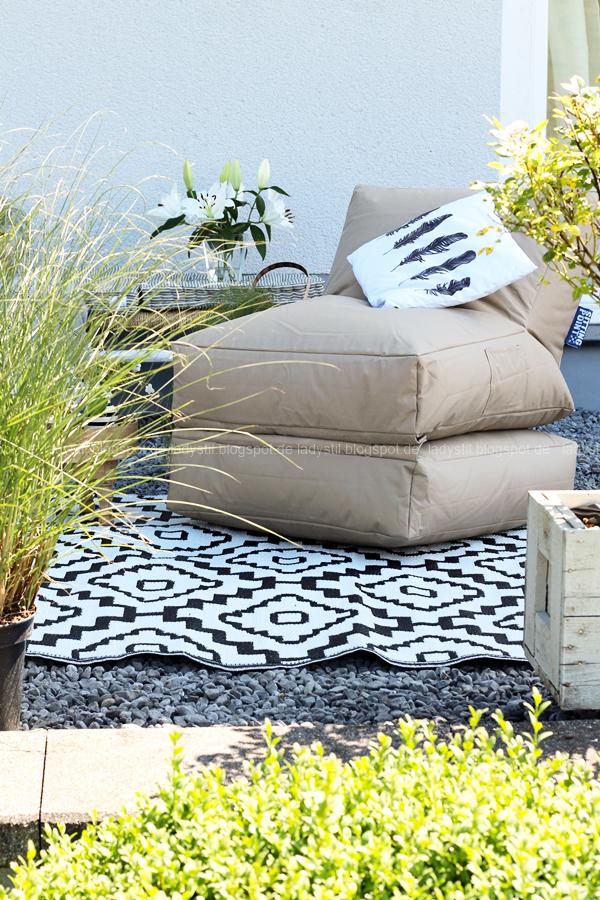 Pop Up Gartensessel, Chillarea im Garten,vom Sessel zur Liege,Outdoorsitzmöbel zum Entspannen,Outdoorteppich schwarz weiß, darauf ein Pop Up Sessel mit Kissen Federmotiv