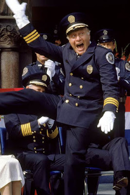 Full shot of cheering George Gaynes as Lassard, wearing police uniform and hat; other officers in background. Warner Bros. via Getty Images file