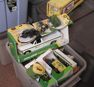 A tote full of John Deere die cast collectible toys.