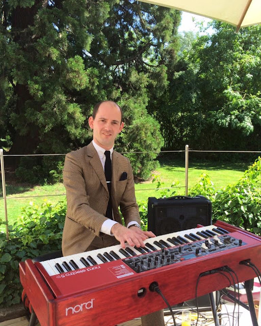 Man in suit playing Nord Electro 5D keyboard on decking at outdoor British wedding