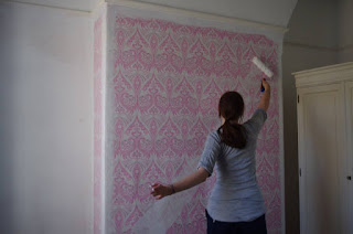 DIY Girl painting over pink wallpaper