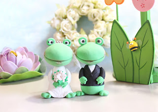 Funny Frog wedding cake toppers, bride wearing a white dress, holding white bouquet with scattered beads; tiara of rhinestones and veil; groom wearing a black jacket
