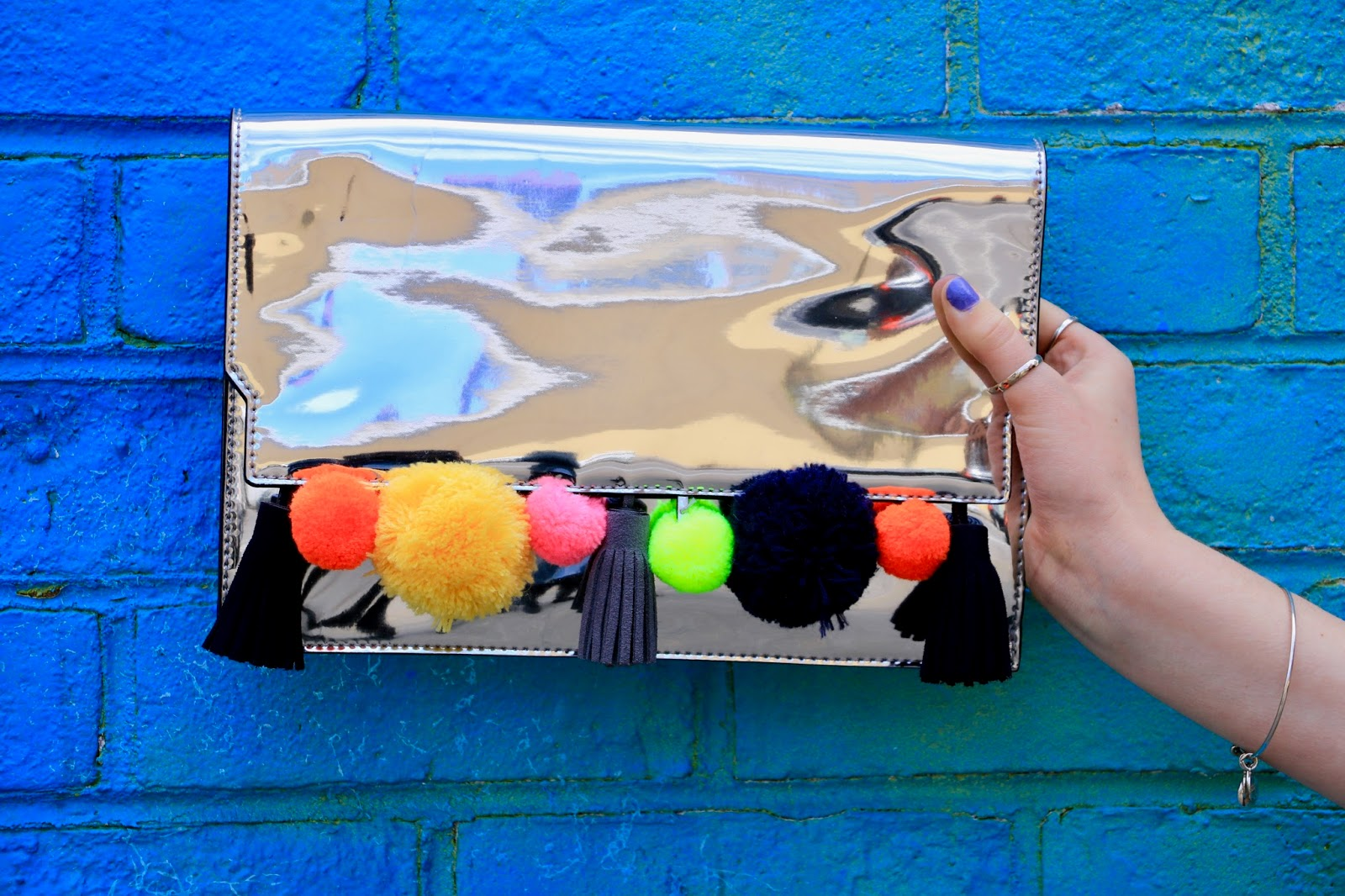Silver metallic Rebecca Minkoff clutch with rainbow pom poms