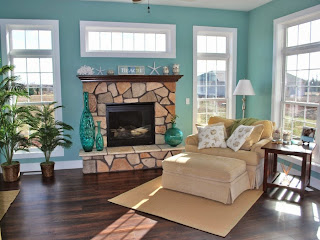 inspiring living room with turquoise wall color and stone fireplace with white nautical decorating items on brown mantel