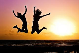 foto de duas pessoas pulando de felicidade, ao pôr-de sol