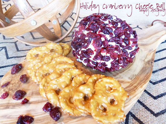 Cranberry Cheese Ball on a wood board with pretzel thins around it