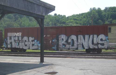 Graffiti words on a brown rail car reading HUGE BONUS