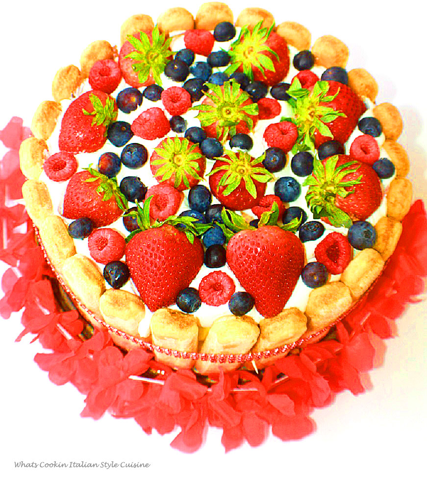 this is a layered cake trifle made in a springform pan. It has cake, lemon pudding, whipped cream, lady fingers around the edges and fresh raspberries, strawberries and blueberries on top. The cake is rich and elegant looking with a faux red diamond band all around and a Hawaiian lei around it on a red dish to serve it on