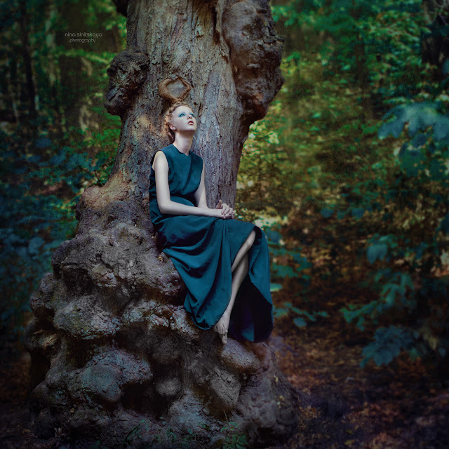 Girl in the long dress sitting on the big twisted tree in the forest