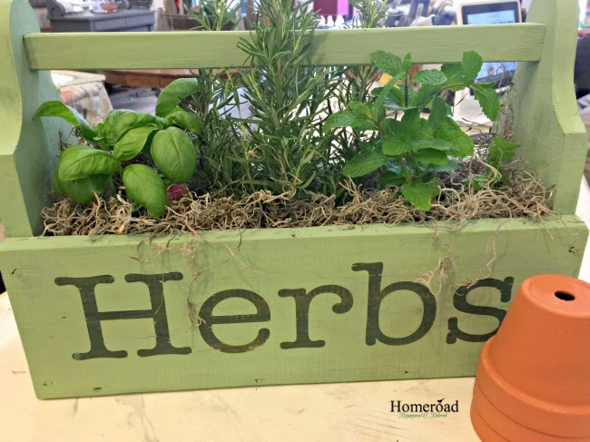 Wooden crate with herbs and a sign font created with vinyl letter stencils.