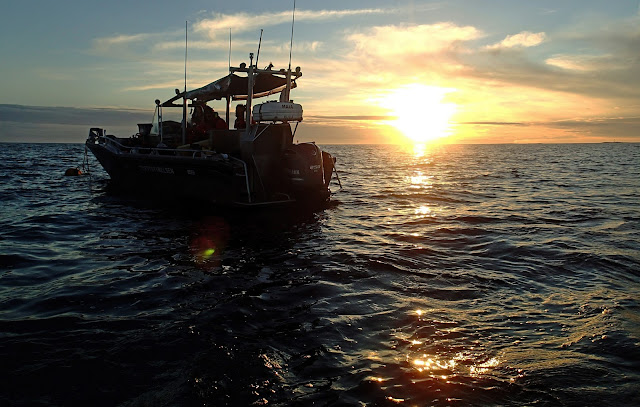 Auringonlasku merellä, vene etualalla.