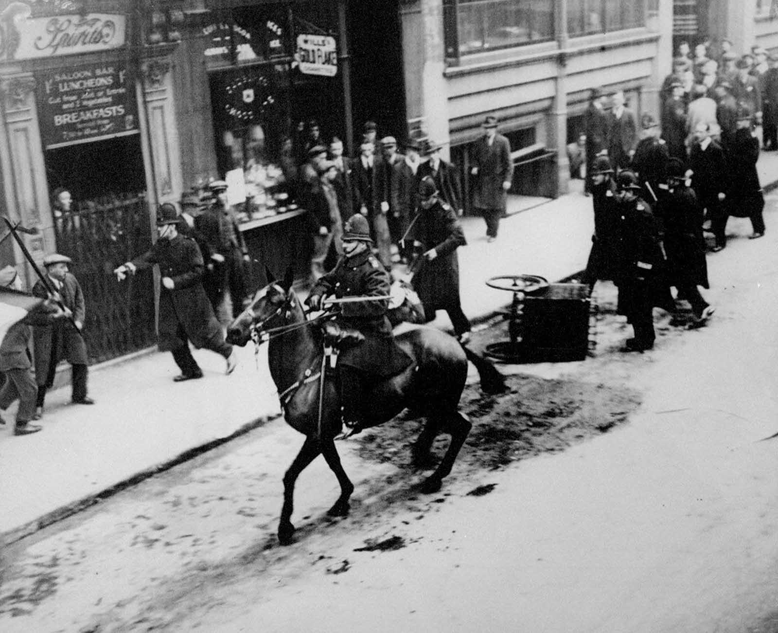 Communist loyalists attempt to stage a riot in London. The horse mounted police officer is armed with a sword. 1930.