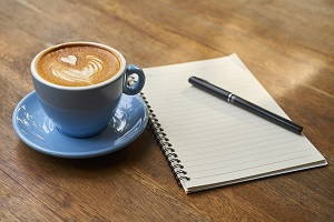Café y cuaderno para escribir una novela