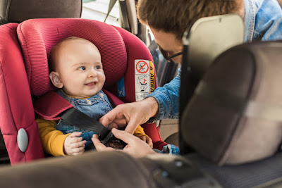 Baby being safely fastened into car seat in Iceland car rental