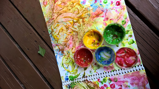 notebook paper painted with bright and colorful finger paints