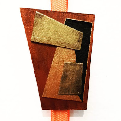 A brooch with geometric shapes in shades of copper, gold, bronze and black displayed on an orange netting ribbon.