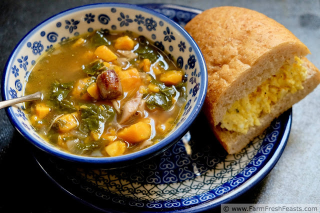 a bowl of chicken, sweet potato and kale soup with an egg salad sandwich on the side