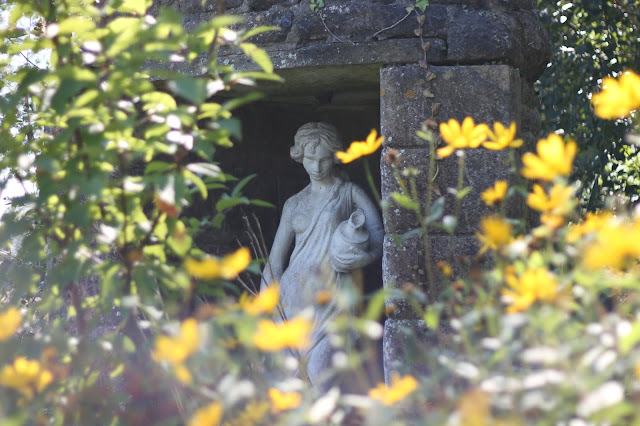 pretty garden at dewstow gardens with statues and yellow flowers